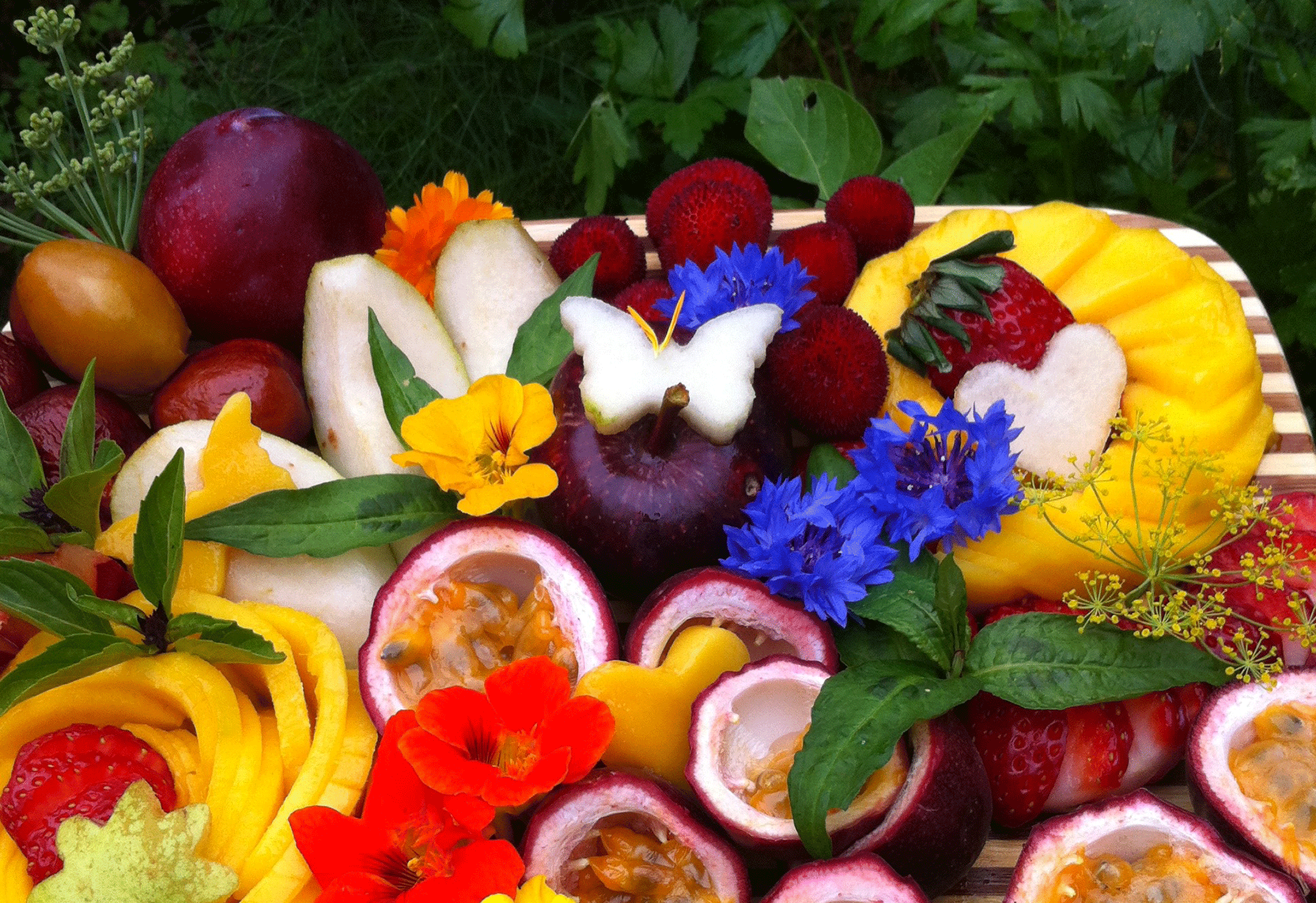 Beautiful fruit platter with tropical and non-tropical fruits, edible flowers, and heart and butterfly shapes cut out of fruit.